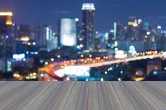 A opinião superior do telhado de madeira do assoalho com bokeh borrado da cidade ilumina-se durante o crepúsculo Imagem de Stock