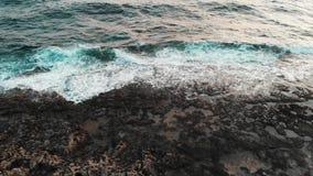 Opinião superior do zangão do litoral com a praia rochosa preta e as ondas enormes bonitas do mar que despedaçam-se em penhascos  video estoque
