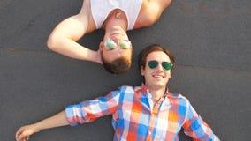 Opinião superior dois homossexual consideráveis nos óculos de sol que encontram-se com expressão da felicidade e da alegria na ca vídeos de arquivo