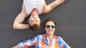 Opinião superior dois indivíduos consideráveis nos óculos de sol que encontram-se com expressão da felicidade e da alegria na car filme