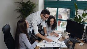 Opinião superior a equipe dos coordenadores novos que discutem algum projeto no fundo do escritório filme