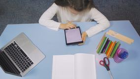 Opinião superior a estudante que estuda na biblioteca que faz após trabalhos de casa das lições com PC da tabuleta Escola primári video estoque