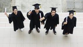 Opinião superior estudantes dos povos com os vestidos e o chapéu da graduação Fotografia de Stock Royalty Free