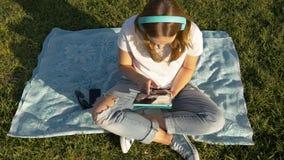 Opinião superior a fêmea nova com dispositivos e fones de ouvido no parque na grama verde imagens de stock
