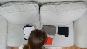 A opinião superior a jovem mulher que prepara-se e que classifica veste-se para a viagem do verão no sofá video estoque