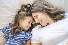 Opinião superior a mãe nova bonita e a sua filha na cama em casa fotos de stock