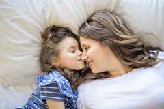 Opinião superior a mãe nova bonita e a sua filha na cama em casa fotos de stock royalty free