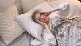 Opinião superior a moça com a dor de cabeça que coloca na cama vídeos de arquivo