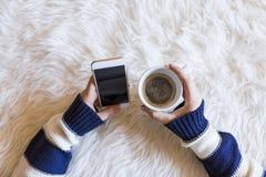 A opinião superior a mulher entrega guardar um telefone esperto sobre o fundo branco Xícara de café além disso lifestyles dentro fotografia de stock