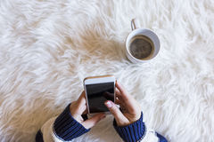 A opinião superior a mulher entrega guardar um telefone esperto sobre o fundo branco Xícara de café além disso lifestyles dentro imagens de stock royalty free