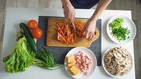 A opinião superior a mulher entrega vegetais do corte em uma placa de madeira para o jantar da pizza na cozinha em casa video estoque