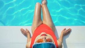 Opinião superior a mulher no tampão e nos óculos de sol que jogam com água perto da associação, férias video estoque