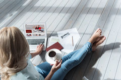 Opinião superior a mulher que guarda o copo de café e que usa o portátil Fotografia de Stock