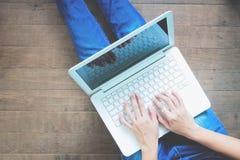 Opinião superior a mulher que usa o portátil que senta-se no assoalho de madeira, conceito do estilo de vida foto de stock
