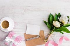 A opinião superior a nota, o envelope de kraft, o copo de café e a peônia vazios floresce sobre o fundo rústico de madeira branco Fotos de Stock