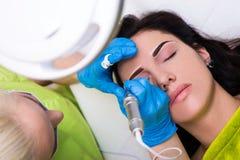 A opinião superior o cosmetologist que aplica o permanent compõe nas sobrancelhas imagens de stock