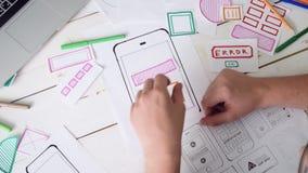 Opinião superior o desenhista de UX que cria a disposição da aplicação do smartphone video estoque