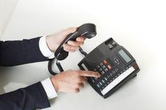 A opinião superior o homem de negócios entrega o disqu para fora em um deskphone preto Imagem de Stock