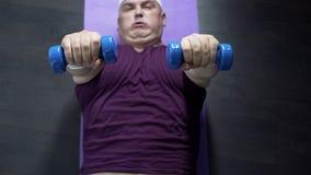 Opinião superior o homem excesso de peso que encontra-se no assoalho e em pesos de levantamento com esforço foto de stock