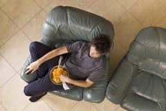 A opinião superior o homem novo olha a televisão e muda os canais ao relaxar fotos de stock royalty free