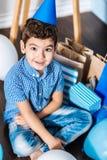 Opinião superior o menino agradável do aniversário cercado por seus presentes Imagem de Stock Royalty Free