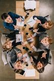 Opinião superior os colegas do negócio que mostram os dedos médios e que sentam-se na tabela fotografia de stock