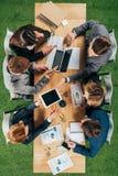 Opinião superior os colegas do negócio que trabalham na tabela com smartphone e tabuleta do portátil imagem de stock royalty free