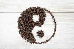 Opinião superior os feijões de café que fazem um símbolo Yin yang na superfície de madeira clara Imagem de Stock