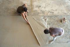 Opinião superior os trabalhadores que fazem o assoalho do cimento com a pá de pedreiro no canteiro de obras Conceito dos trabalho foto de stock