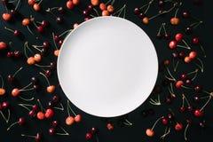 opinião superior a placa branca redonda vazia e cerejas doces fotografia de stock royalty free