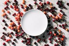 opinião superior a placa branca redonda vazia e cerejas doces maduras foto de stock royalty free