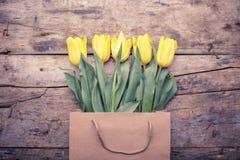 Opinião superior tulipas amarelas no saco na tabela de madeira Imagens de Stock