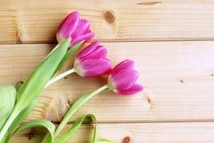 A opinião superior tulipas cor-de-rosa arranjou na linha sobre o fundo de madeira Cartão de cumprimentos da mola com as tulipas p Imagem de Stock