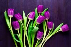 Opinião superior tulipas roxas no fundo roxo de madeira Fotos de Stock Royalty Free