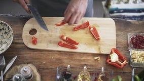 Opinião superior um cozinheiro chefe que corta uma pimenta de sino vermelha vídeos de arquivo
