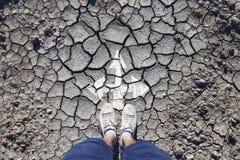 Opinião superior um homem que está em solo rachado com setas Imagem de Stock