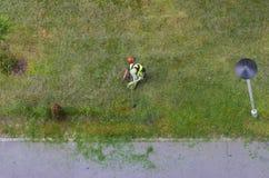 Opinião superior uma grama do corte do landscaper da cidade com cortador de grama; Foto de Stock Royalty Free