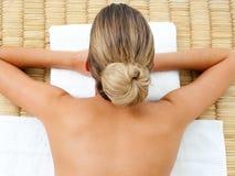 Opinião superior uma mulher que encontra-se em uma tabela da massagem foto de stock