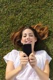 Opinião superior uma mulher que encontra-se na grama que texting em um telefone esperto Fotografia de Stock