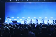 Opinião traseira a audiência sobre os oradores na fase na reunião da sala de conferências ou do seminário, no negócio e na educaç fotos de stock