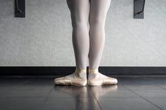 Opinião traseira a bailarina do dançarino de bailado na barra na classe de dança que está na primeira posição imagens de stock