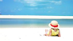 Opinião traseira a criança no chapéu na praia durante férias tropicais das caraíbas Movimento lento vídeos de arquivo