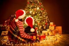 Opinião traseira traseira da família do Natal que olha à árvore, à mãe e à criança do Xmas em Red Hat fotografia de stock royalty free