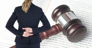A opinião traseira da seção mestra a mulher de negócios com dedos cruzou a posição na frente do martelo e do livro de lei fotografia de stock