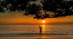 Opinião traseira da silhueta a mulher 'sexy' que olha o por do sol bonito na praia tropical do paraíso Biquini do desgaste da men foto de stock