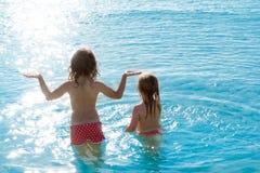 Opinião traseira das meninas das crianças na praia no por do sol Fotografia de Stock