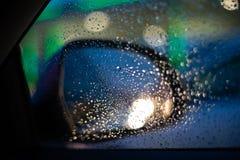 Opinião traseira direita do espelho do carro do interior do carro com gotas na janela imagens de stock royalty free