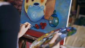 Opinião traseira do close-up a mulher do artista com a escova que pinta ainda a imagem da vida na lona no estúdio da arte Fotos de Stock