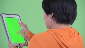 Opinião traseira do close up a mulher asiática excesso de peso nova feliz que usa a tabuleta digital pronta para o gym video estoque