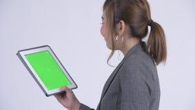 Opinião traseira do close up a mulher de negócios asiática feliz nova que usa a tabuleta digital vídeos de arquivo